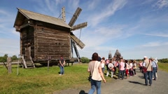 Tourists at the old windmill on Kizhi Island in Russia Stock Footage