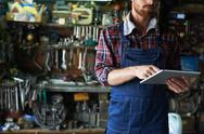 Mechanic using touchpad while working in workshop Stock Photos