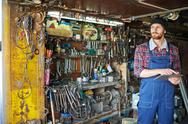 Mechanic standing in his repair shop with digital tablet Stock Photos