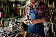 Plumber looking at spare part in his workshop Stock Photos