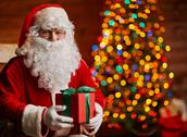 Santa Claus posing with gift box against fritree Stock Photos