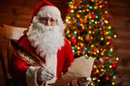 Santa Claus with paper and weather looking at camera and smiling Stock Photos