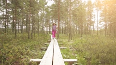 Little beautiful girl walks on swamp in Estonia Stock Footage