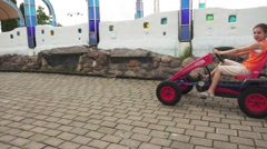 Beautiful little girl rides mechanical go-kart Stock Footage
