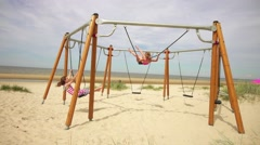 Beautiful little girl on swing Baltic Sea Stock Footage