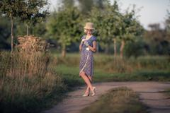 Retro 1920s summer fashion woman with blue dress and straw hat standing on ru Kuvituskuvat