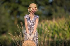 Vintage 1920s summer fashion woman with blue dress and straw hat standing wit Kuvituskuvat