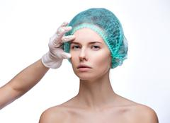 Medical examination face of beautiful woman by hands in glove - close-up Stock Photos