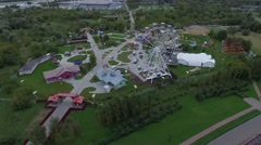 Aerial View of the Amusement Park, the Ferris Wheel, the Garden and the City Stock Footage