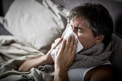 Sick man with cold lying in bed and blow nose. Stock Photos