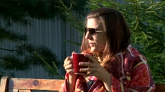 Beautiful girl wrapped in plaid drinking cup of coffee Stock Footage
