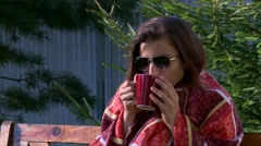 Pretty girl in sunglasses covered with warm plaid drinking hot tea Stock Footage