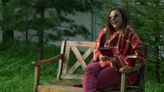 Girl covered with warm plaid reading tablet pc and laughing, autumn park Stock Footage