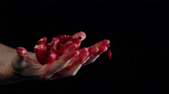 Mans hands crushing pomegranate against black background Stock Footage