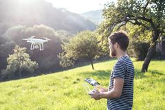 Young hipster man with flying drone. Sunny green nature Stock Photos