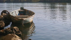 Old moored boat in a river, with trees on the other side Stock Footage