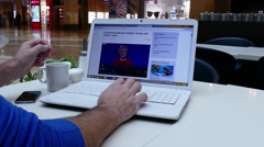 Man in shopping mall reading BBC news on laptop Stock Footage