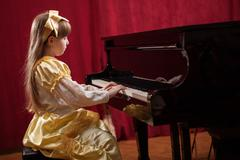 Little girl playing classical piano Stock Photos