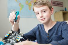 Boy Assembling Robotic Kit In Bedroom Stock Photos