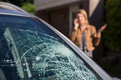 Woman Phoning For Help After Car Windshield Has Broken Stock Photos