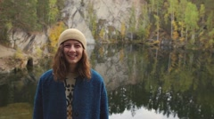 Girl in the hat smiling in front of lake. Autumn, quarry Stock Footage