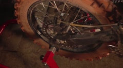 A mechanic repairing motorcycle racing lifts the rear wheel on the stand Stock Footage