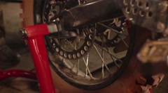 The mechanic is repairing a motorcycle racing rear wheel lifts Stock Footage