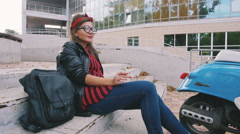 Young hipster woman in glasses sitting on stairs and smoking cigarette, slow mot Stock Footage