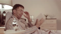 Man in spectacles is sitting in bed with a book and laughing his pleasure Stock Footage