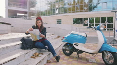 Young hipster woman sitting on a stairs with map with vintage scooter beside her Stock Footage