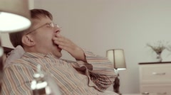 Yawning young man puts his spectacles on the nightstand and goes to sleep Stock Footage