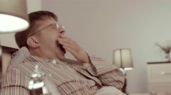 Sleepy young man yawning in bed, putting spectacles away and going to sleep Stock Footage