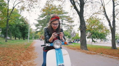Happy young hipster woman playing smart phone games in park on her vintage scoot Stock Footage