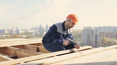 Worker on a roof with electric drill installing tile on wooden house Stock Footage