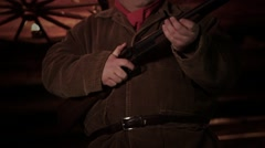A man holds a shot gun and slowly points it towards camera. Stock Footage