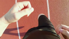 TOP VIEW: Man runs on a stadium track (slow motion) Stock Footage