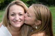 Portrait of young girl giving kiss to her mom Stock Photos