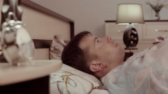 Young man lying in his bed is frightened Stock Footage
