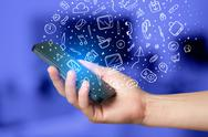 Hand holding smartphone with hand drawn media icons and symbols Stock Photos