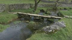 4K Small Stone Bridge Over Malham Beck Stream by Malham Cove Cliff  Trees Stock Footage