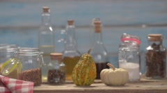 Small decorative pumpkin, glass bottles and jars with oil and spices. Stock Footage