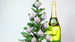 New Year's balls on a New Year tree and a huge bottle of sparkling wine Stock Footage