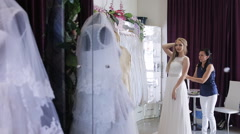 Girl chooses a wedding dress in a wedding salon Stock Footage