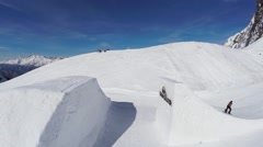 Quadrocopter shoot snowboarder jump from springboard. Mountains. Blue sky. Sport Stock Footage