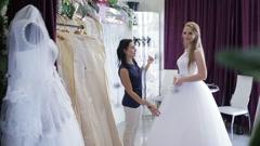 Woman choosing wedding dress in shop Stock Footage