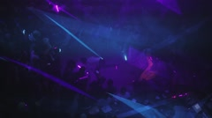 Beams from laser show on party in nightclub. Man in white shirt break dance Stock Footage
