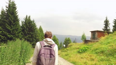 Young male tourist with rucksack descending alone on a mountain road in summer Stock Footage