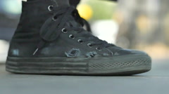 A young man ties his high-top shoes before riding his skateboard, slow motion. Stock Footage