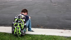 Sad, lonely boy sits on a curb at school Stock Footage