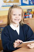 Female Elementary School Pupil Using Digital Tablet In Class Stock Photos